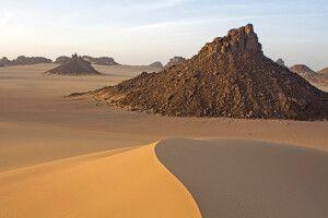 Felsformationen und gelb-rote Dünen der Sahara